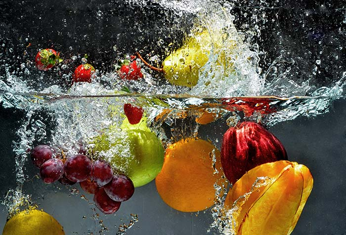 Fruits and vegetables splash into water