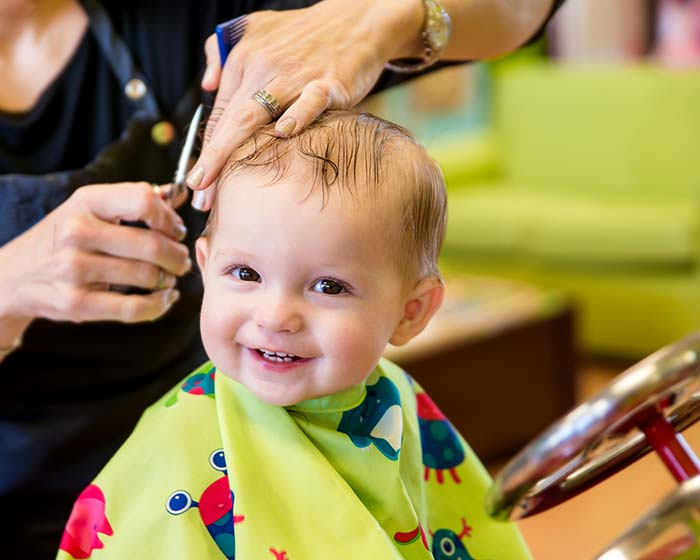 Smiley baby cutting hair